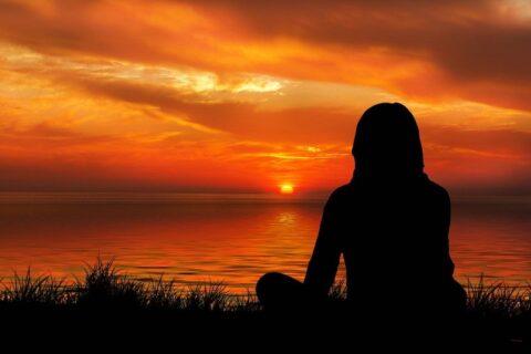 Frau sitzt am Meer und blickt auf den Horizont- Hypnotische Trance im Alltag |wirkungsvolle Beeinflussung